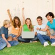 Group of teens with laptop hands raised for success or winning — Stock Photo