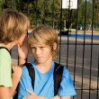 School kids whispering problems - Stock Photo
