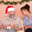 Senior christmas with carer or grandchild wih gift — Stock Photo