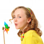 Pretty girl blowing windmill — Stock Photo