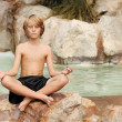 Child meditating in yoga position — Stockfoto