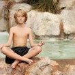 Child meditating in yoga position — Stock Photo