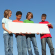 Foto Stock: Group of diverse children holding blank white poster