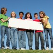 Group of diverse children holding blank white poster - Stock Photo
