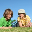 Kids playing outdoors with magnifying, glass — Stock Photo