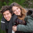 Happy smiling winter teen couple in piggy back - Stockfoto