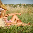 Young woman relaxing in field outdoors in summer - Stockfoto