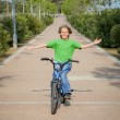 Confident child riding bike or bicycle - Stockfoto