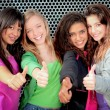 Happy diverse teen girls showing thumbs up - Stockfoto