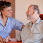 Elderly man with nurse carer or granddaughter — Stock Photo