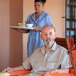 Senior with carer or nurse bringing meal - Stockfoto