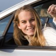 Stock Photo: Womshowing key to new or hire rental car