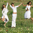 Group of happy young women jumping on summer or spring — Стоковая фотография