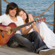 Happy couple with guitar - Stockfoto