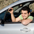 Young man with key to new or rental car - Stock Photo