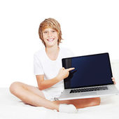 Kid with laptop computer pointing at screen — Stock Photo
