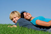 Happy smiling, teen couple laying on grass in summer — Stock Photo