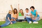 Grupp av tonåringar med laptop händerna upp för framgång eller vinnande — Stockfoto