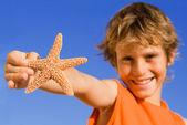 Summer child focus on starfish — Stock Photo