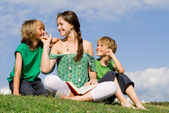 Woman reading to children outdoors — Stock Photo