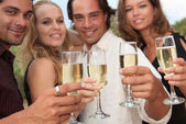 Group of toasting with champagne at party — Stock Photo