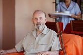 Senior elderly man with carer serving meal — Stock Photo