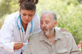 Nurse or doctor taking temperature of senior patient — Stok fotoğraf
