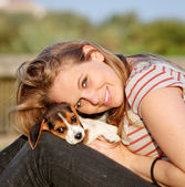 Happy teen young woman with her pet puppy dog — Stock Photo