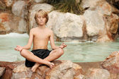 Child meditating in yoga position — Стоковое фото