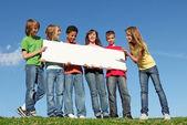 Grupa różnych dzieci przytrzymanie puste plakat biały — Zdjęcie stockowe