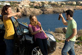 Underage kids drinking alcohol and partying outdoors with car — Stock Photo