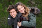 Happy smiling winter teen couple in piggy back — Stock Photo