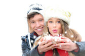 Fantasy happy winter couple blowing a christmas wish — Stock Photo