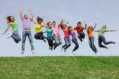 Szczęśliwy uśmiechający się różnorodne mieszane rasy grupa skoki — Zdjęcie stockowe