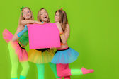 Fashion girls in neon clothing holding blank pink billboard — Stock Photo