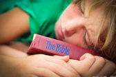 Christian child sleeping with well worn and read bible — Stock Photo