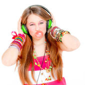 Funky girl listening to music and blowing bubble with gum — Stock Photo