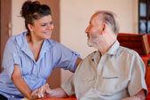 äldre man med sjuksköterska vårdare eller barnbarn — Stockfoto