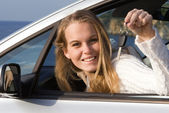 Woman showing key to new or hire rental car — Stock Photo