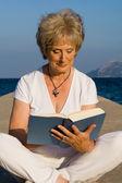 Healthy senior reading outdoors on summer vacation — Stock Photo