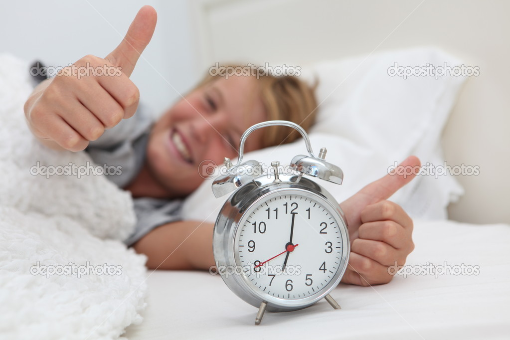 Happy child waking up with alarm clock  Stock Photo #6361417