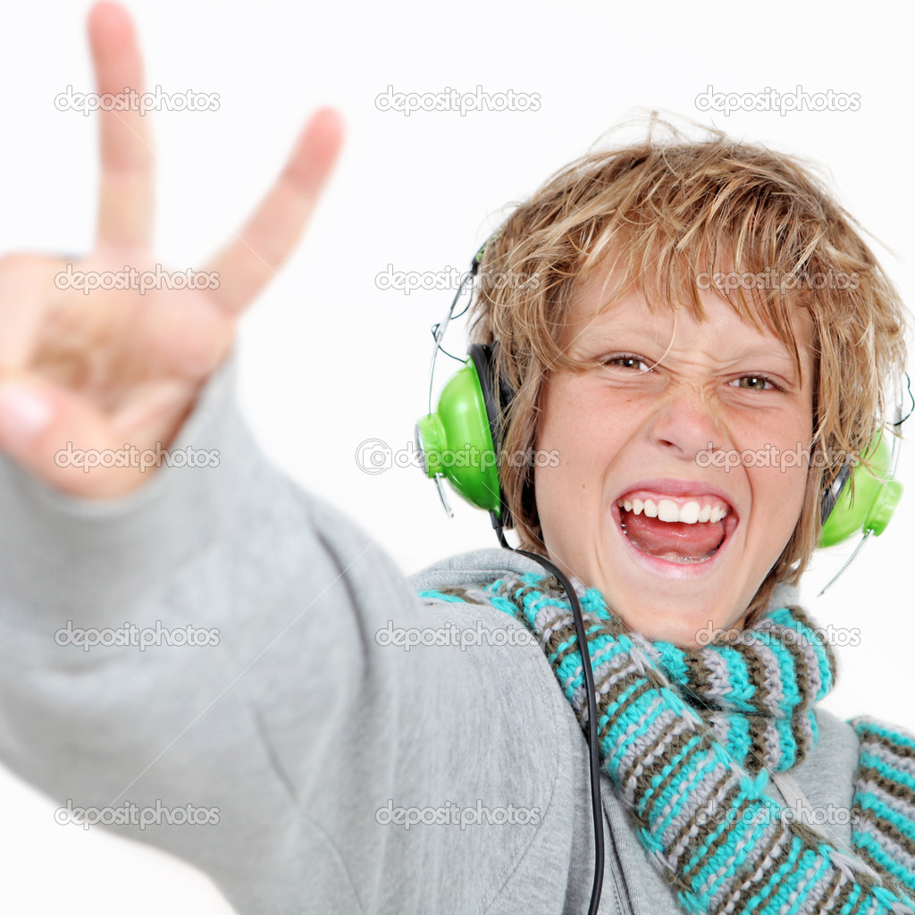 Happy kid doing v sign and listening to music wearing headphones. — Stock Photo #6361448