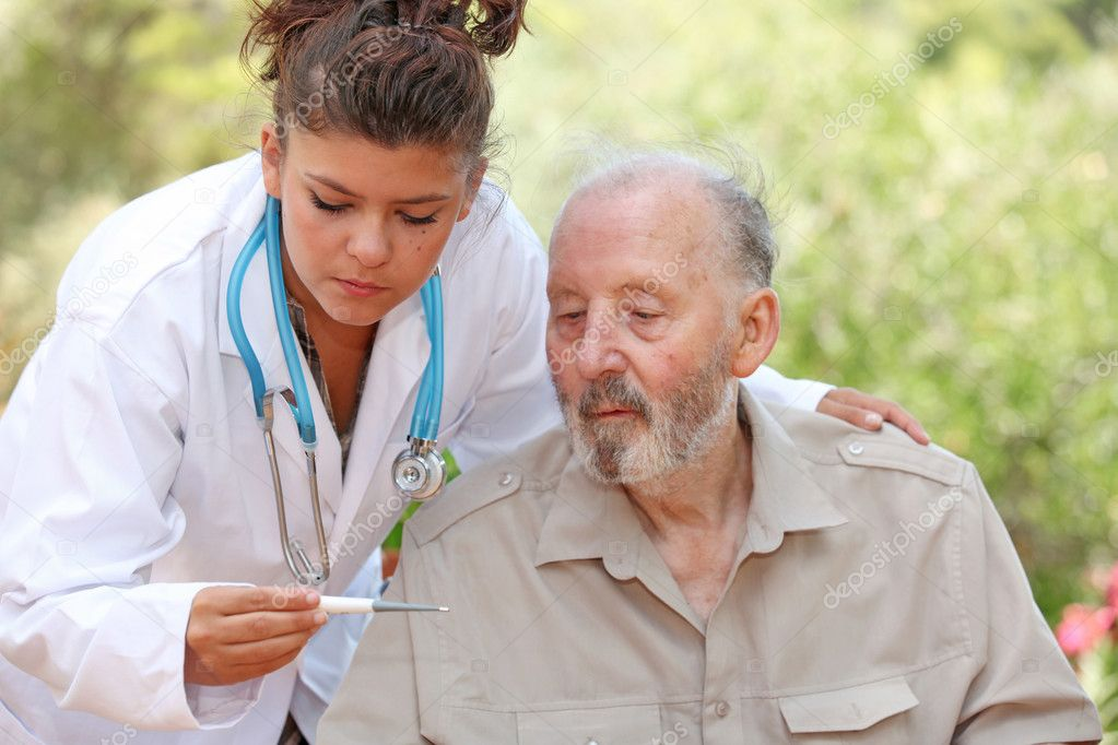 Nurse or doctor taking temperature of senior ill patient  Stock Photo #6361557