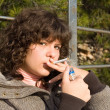 Teen girl smoking cigarette - Stock Photo