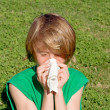 Child with hay fever allergy sneezing and blowing nose outdoors — Stock Photo