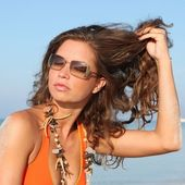 Beautiful woman on vacation showing hair — Stock Photo