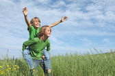 Healthy happy fit active kids playing piggyback outside in summer — Stock Photo