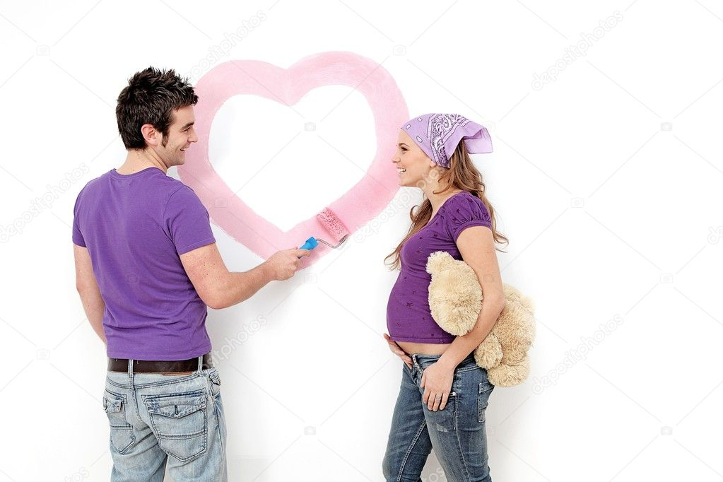 Young couple, husband and pregnant wife painting nursery wall. — Stock Photo #6409166