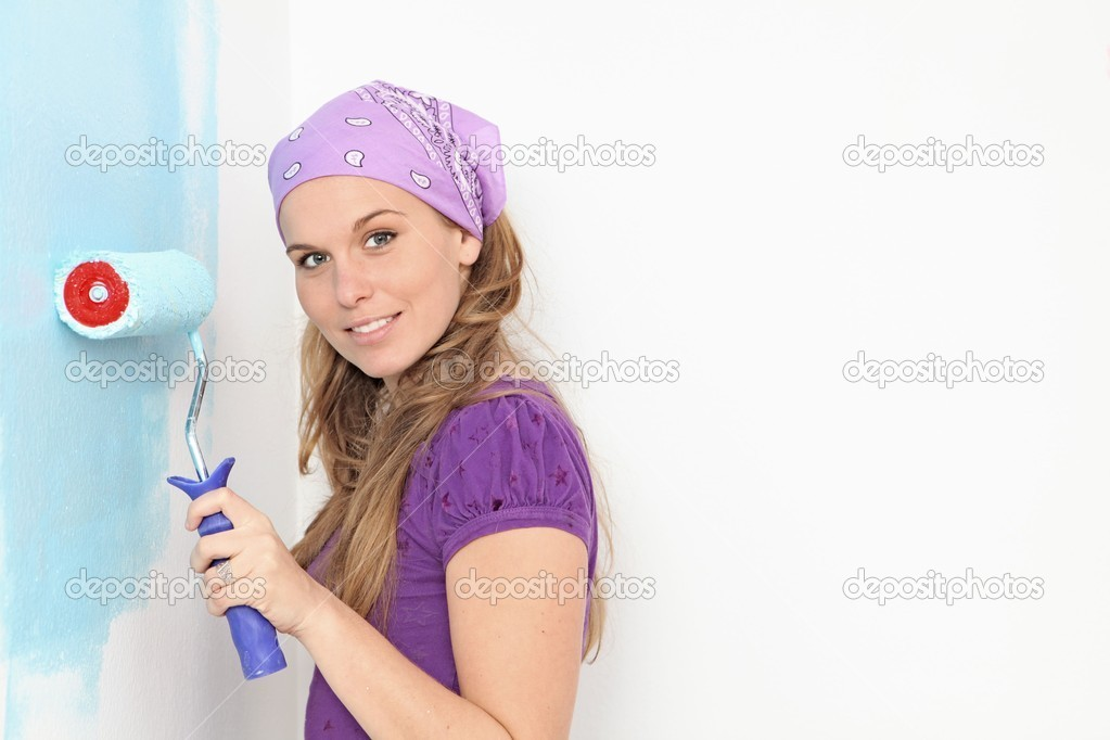 Woman painting home nursery wall with roller paint  Stock Photo #6409170