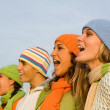 Group of carolers or carol singers singing or sports spectators cheering - Stock Photo